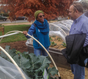 Farmer and customer talking in front of greenhouse full of leafy green vegetables