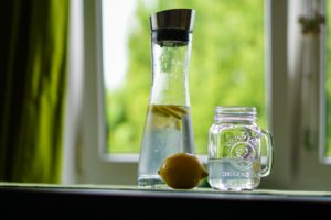 Carafe of water with lemon slices. In front of this are a whole lemon next to a glass mug of water.