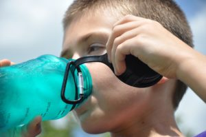 Child drinking from blue refillable water bottle, outdoors.