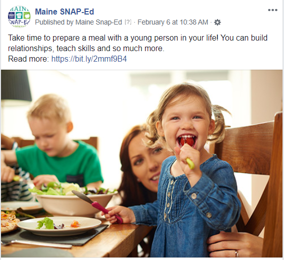 Image of an adult and two children sitting at a dining table. The table is set with a garden salad and the adult is smiling at one of the children while they eat a bite of salad with a happy expression.